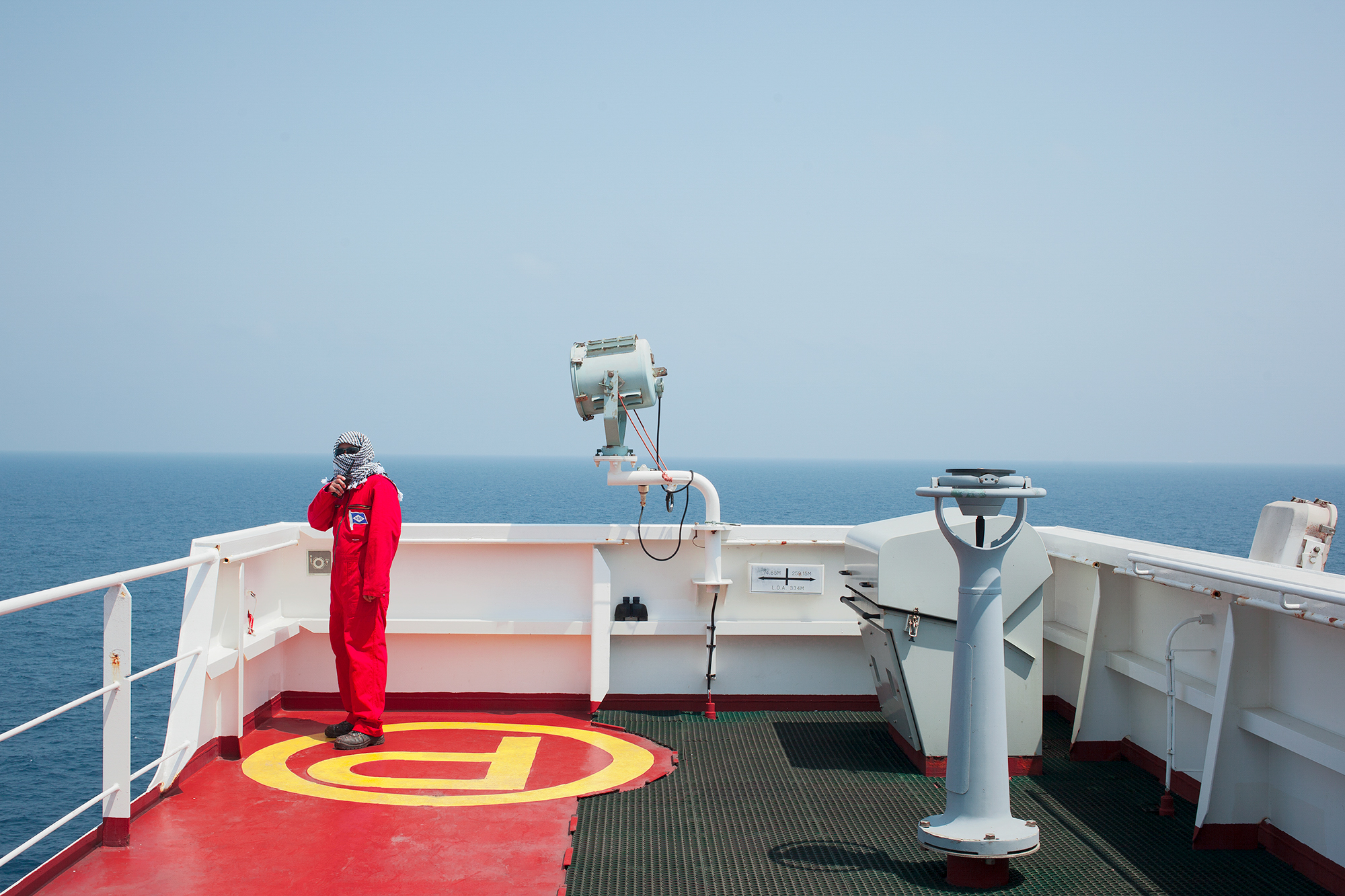 An employee on security watch aboard a Chinese-manufactured vessel, the Gulf of Aden, 2017.