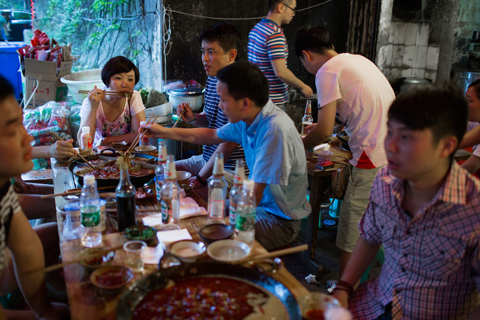 "The group at the end of the table eats hotpot from a nine-section bowl, a Chongqing specialty. Though they live in the neighborhood, members of the group said that this was the first time they'd been to Gang Shan Zhazha because the line is usually too long. Their favorite ingredients of the night were cow stomach, cow intestine, and duck intestine. Xiao Feng, seated at the end of the table, said ""We [Chongqingers] like hot food, but this is very spicy for us."""