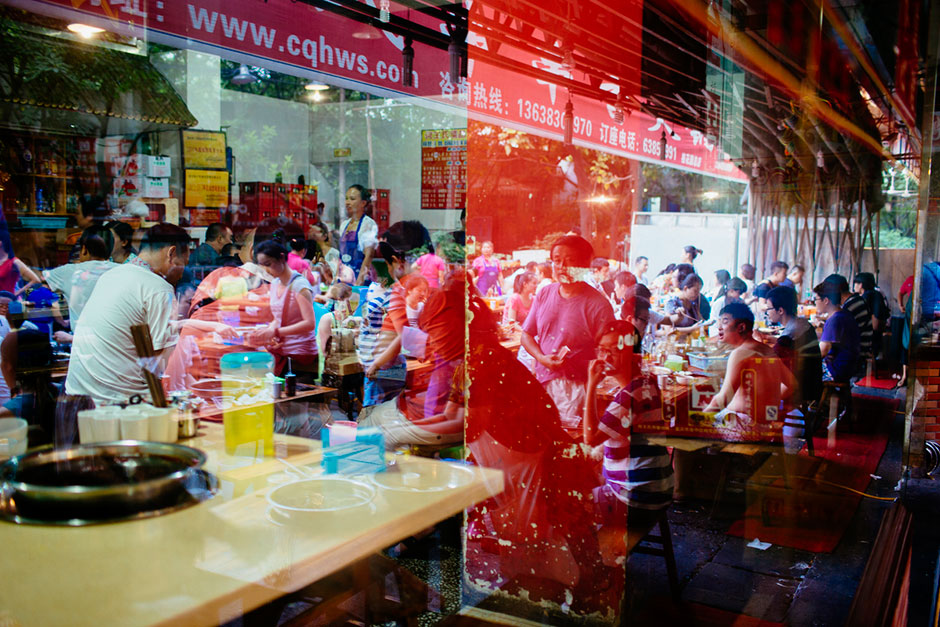 Crowds seated indoors blend with those outdoors in a window reflection at Gang Shan Zhazha, a popular street-side hotpot restaurant on Tiyu Road.