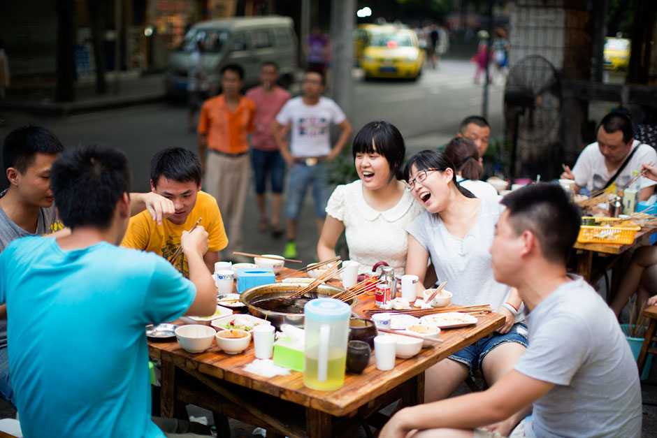 "A group of friends who live in the neighborhood eat at He Wang and Shi's Skewers and Fragrant Hot Pot, a skewer-style hotpot restaurant popular with locals. One of the diners said, ""We like the atmosphere. It's a typical Chongqing place: friends sit together and it's hot out and you all sweat together."""