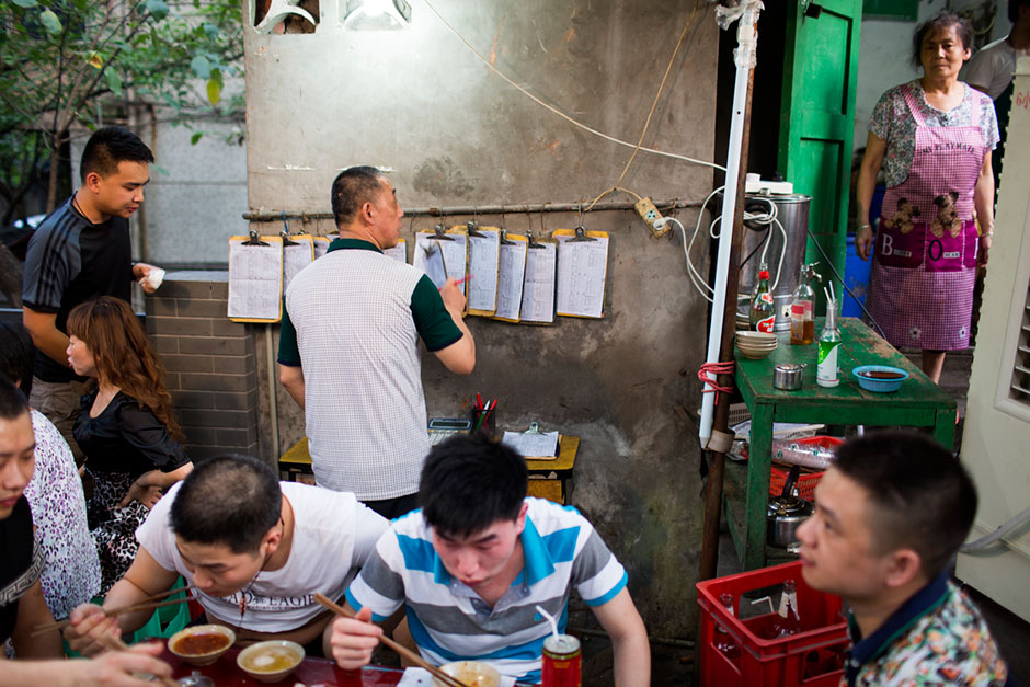 A group eats hotpot out of a split pot in an alley above Tiyu Road as the staff relay orders to the kitchen off hanging clipboards.