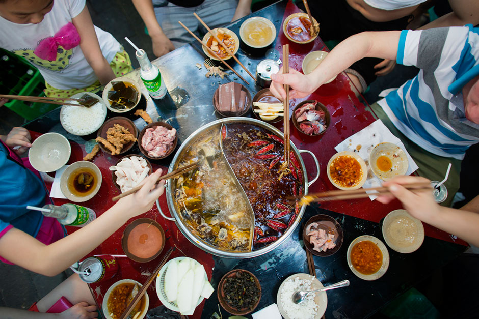 A group eats hotpot out of a split pot that separates the reddish, spicy from not spicy broth at An Pang Hotpot in an alley above Tiyu Road.