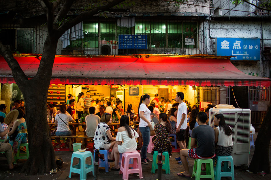 """As the evening dinner rush begins, a crowd forms outside Gang Shan Zhazha, a popular street-side hotpot restaurant on Tiyu Road in the central Yuzhong district of Chongqing. The restaurant sits on the site of a former neighborhood garbage collection point and """"<em>zhazha</em>"""" is local slang for """"garbage."""""""