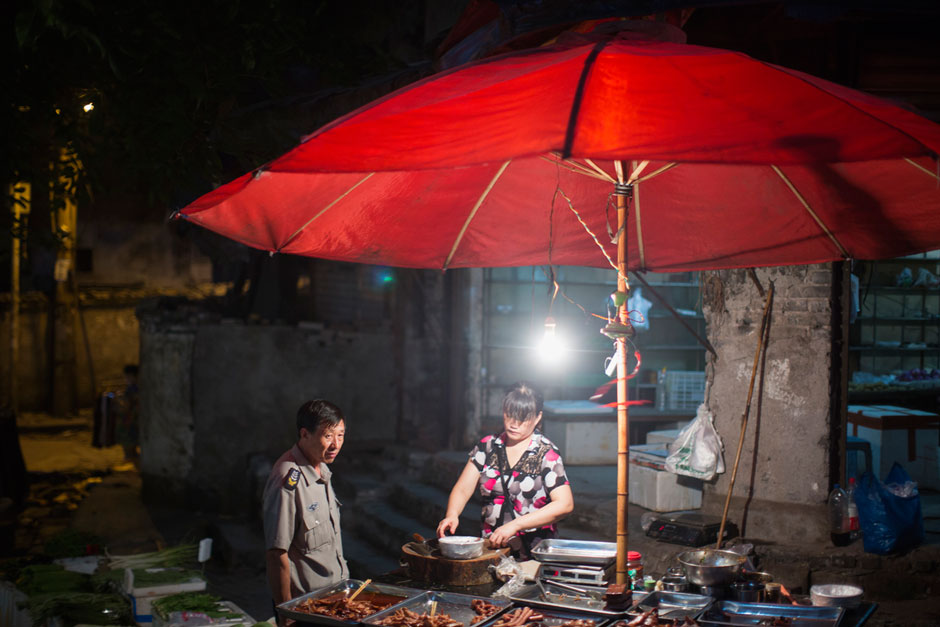 A woman sells chicken and duck pieces at a street stall at the bottom of Shibati.