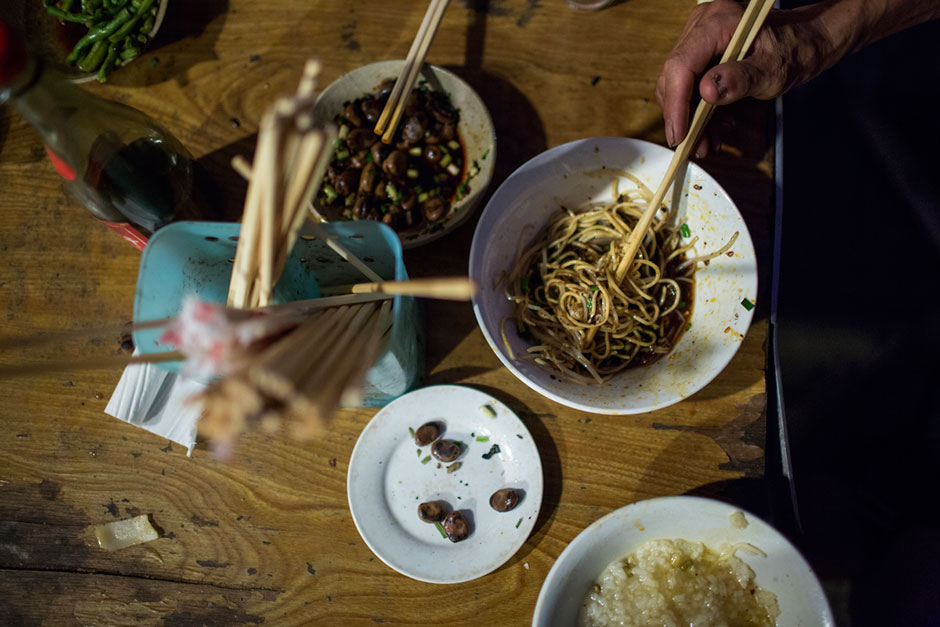 """Bowls of fried noodles and <em>xifan</em>, rice porridge or congee, are consumed at a small unnamed outdoor noodle cafe at the bottom of Shibati. The cook, Tong Suchun, has been in operation for about 20 years. At the time, the neighborhood was slated for redevelopment and Tong said he didn't know what he would do after the restaurant closed. """"I'll take a break,"""" he says, """"and then find something new."""" The restaurant typically serves a couple hundred people in a night. Most spending about 15 RMB, or U.S.$2.40."""