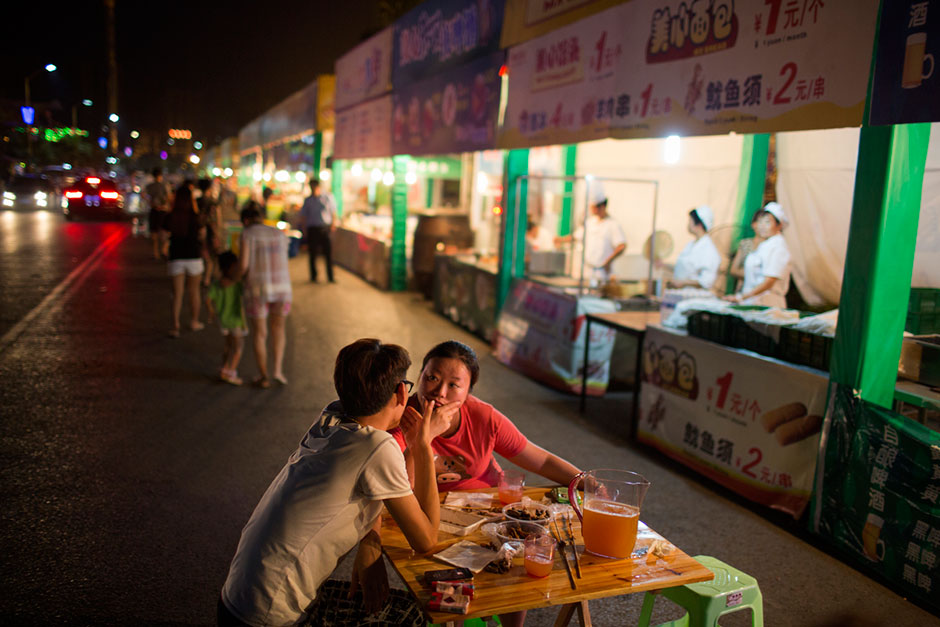 A couple eats lamb and chicken skewers and drinks beer from a food stall near the carnival on Meixin Foreigner Street, a sprawling amusement and oddity park in northeastern Chongqing. The park is popular among working-class Chongqingers. Meat skewers cost 1 RMB each.