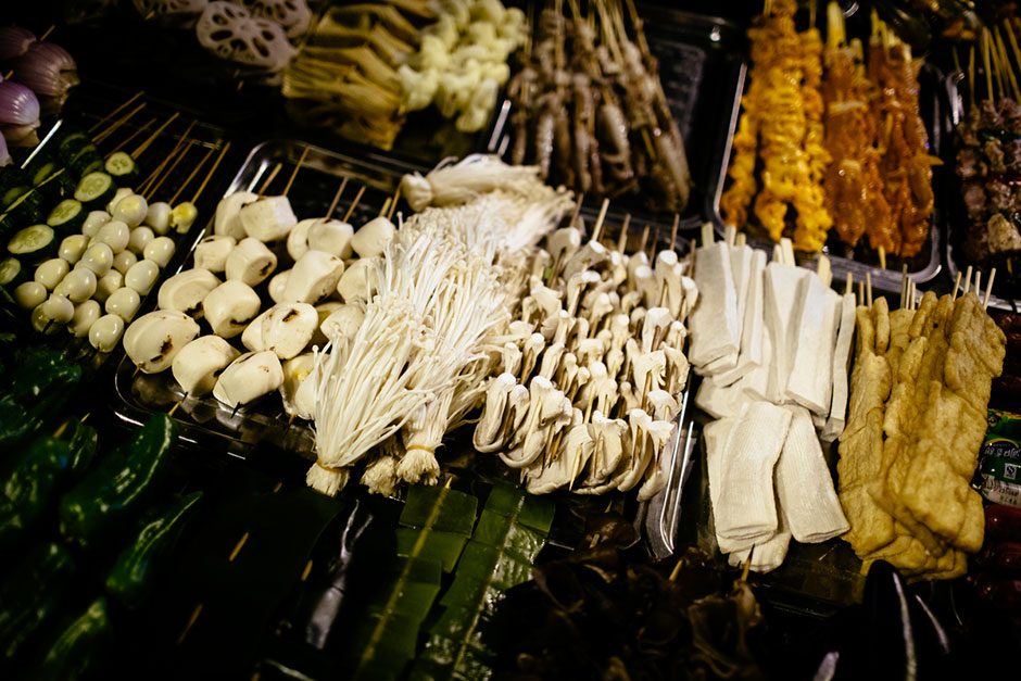 Street-side <em>shaokao</em> cooks work on Tiyu Road. The road is lined with street-side <em>shaokao</em> and hotpot restaurants.