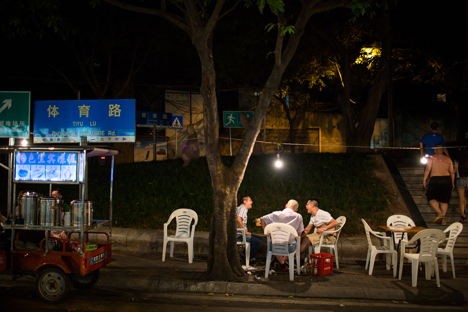 Men drink beer at a street-side <em>shaokao</em> spot on Tiyu Road. <em>Shaokao</em> is a style of barbecue in which patrons choose a variety of raw meats and vegetables to have spiced and cooked. In Chongqing, most <em>shaokao</em> cooks mix all of the ingredients together after barbecuing and add garlic, green onions, hot peppers, and other flavors.