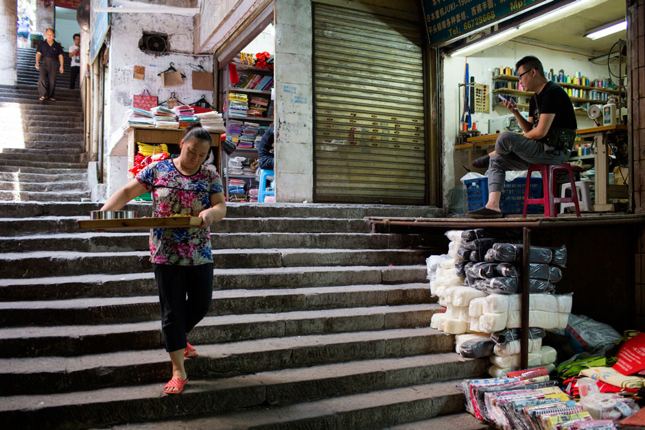 A restaurant worker takes lunch to a stall in a market off Shaanxi Road.