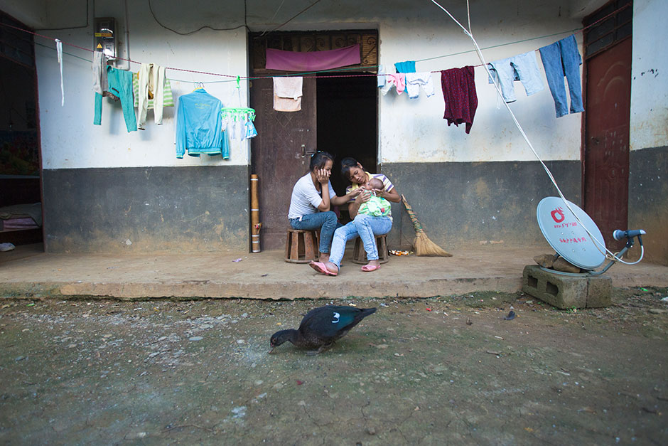 Cai and her mother-in-law play with Cai's baby in front of their house, in Guangdong village, Mengla county.