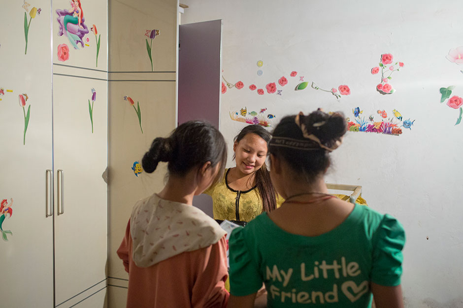 "Jie talks with two neighborhood girls in her room decorated with stickers from the Disney movie ""The Little Mermaid"" and other designs."