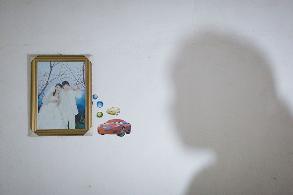 Jie's shadow falls across her bedroom wall near her and her husband's wedding photo. At age 13, Jie was six months pregnant. Her husband is five years older than her.