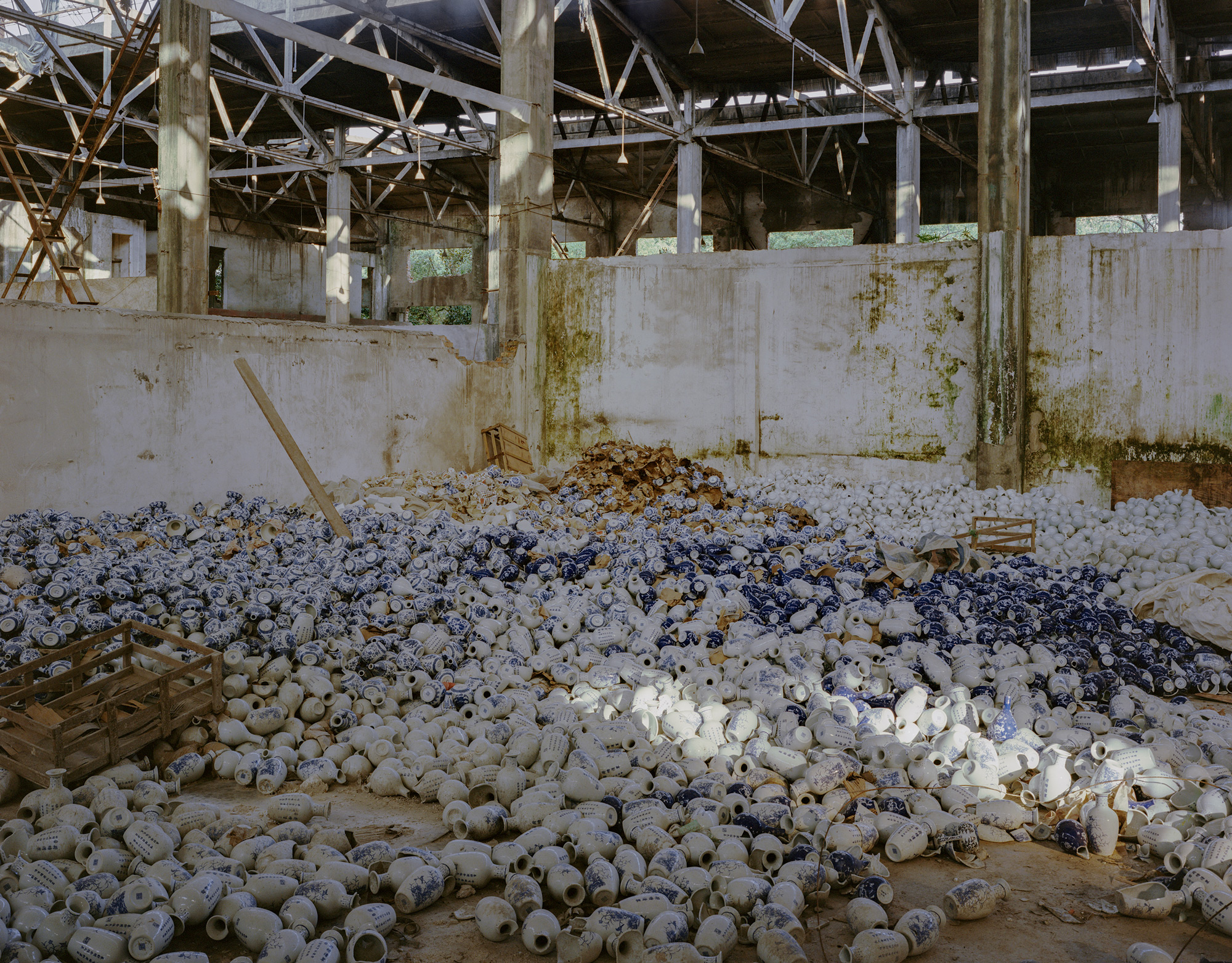 Bottles lay strewn across the floor of a porcelain factory in Jingdezhen city, Jiangxi province, July 2017. Jingdezhen is the historic center of Chinese porcelain production, famous for its high-quality kaolin reserves. However, as kaolin reserves have been depleted, hundreds of mining and production companies have been shuttered over the past two decades.