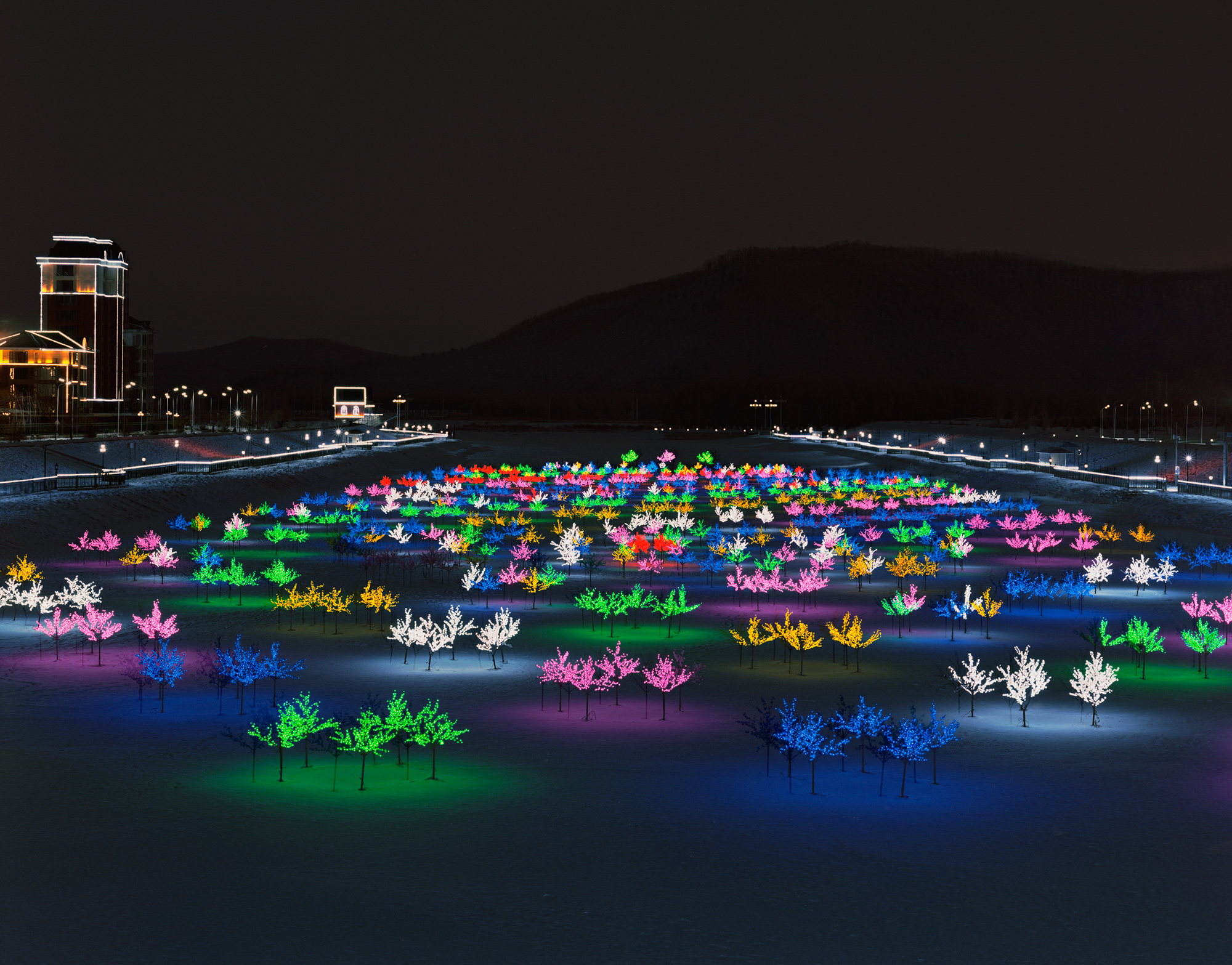 Plastic trees with colorful light bulbs glow on a frozen river in Yichun.