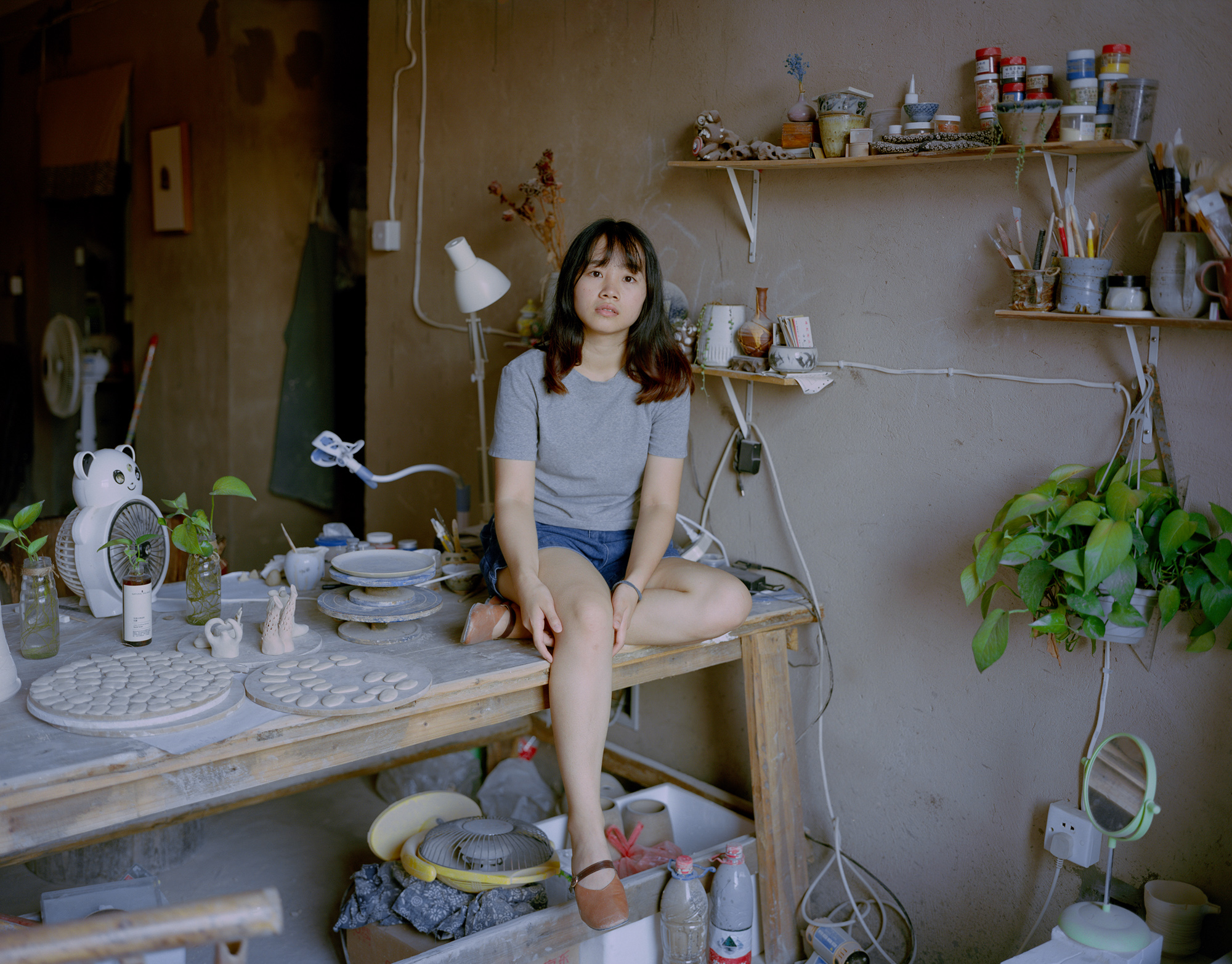 Liang Zhuanshan, a 24-year-old porcelain artist, sits in her studio in Jingdezhen. Despite the clay shortage, Jingdezhen has managed to rejuvenate its art and education industry. Studios and workshops have opened one after another in recent years, and have attracted many artisans.