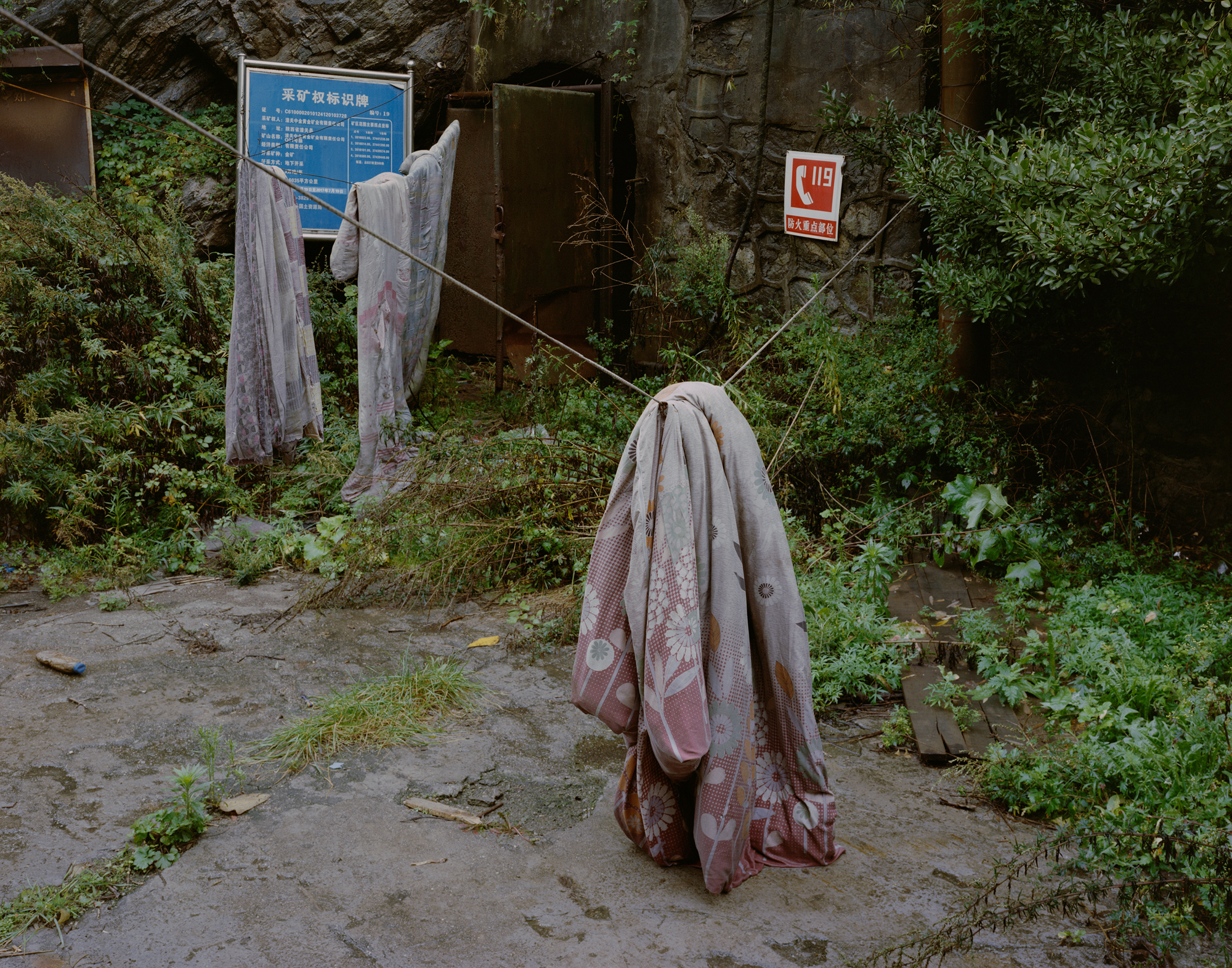Outside an abandoned gold mine, unclaimed quilts hang on a clothesline, in Tongguan.