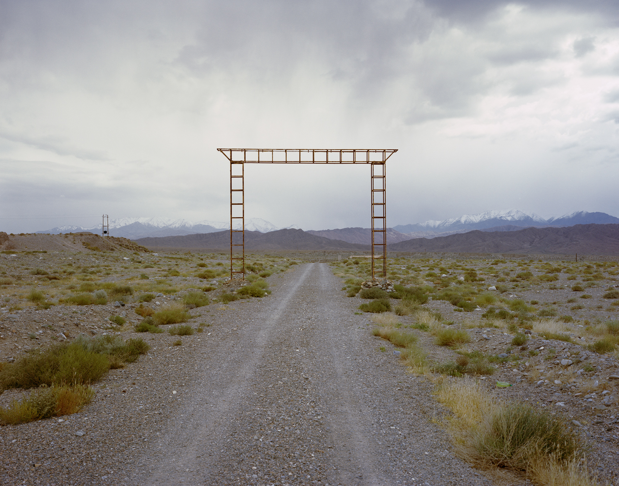 A gate sits on a road at the outskirts of Yumen, at the edge of the Gobi Desert between the Qilian and Beishan mountains. High-speed winds blow through the valley. Over the past decade, Yumen has constructed several giant wind farms, in an attempt to transform its energy production into something more sustainable.