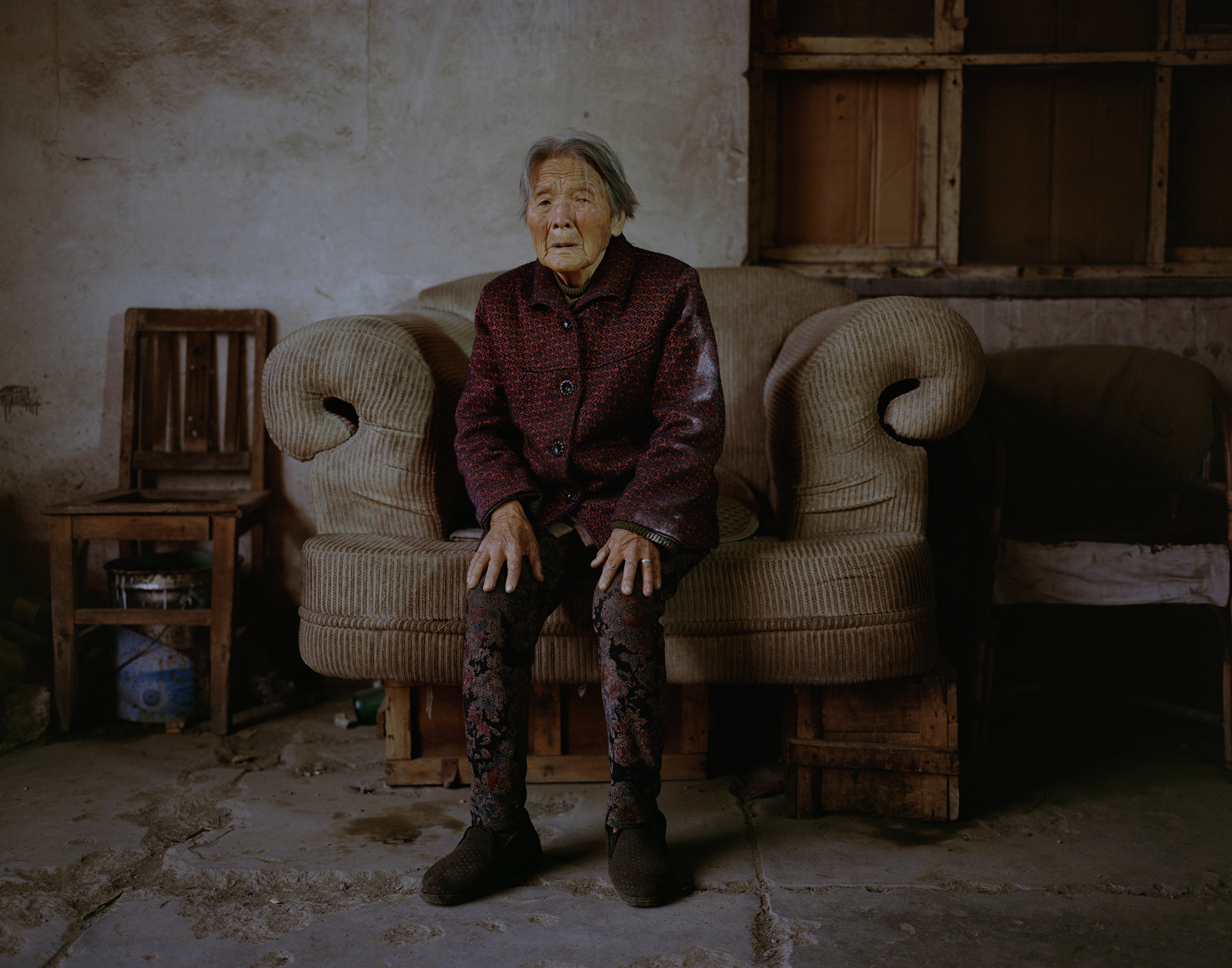 Ma Yulan, 82, sits in the hallway of her apartment building in Xiahuayuan. Ma moved here with her son 30 years ago when he found a job at a coal mine. During the local coal industry's peak, 89 mines were operational. Now there are fewer than 10.