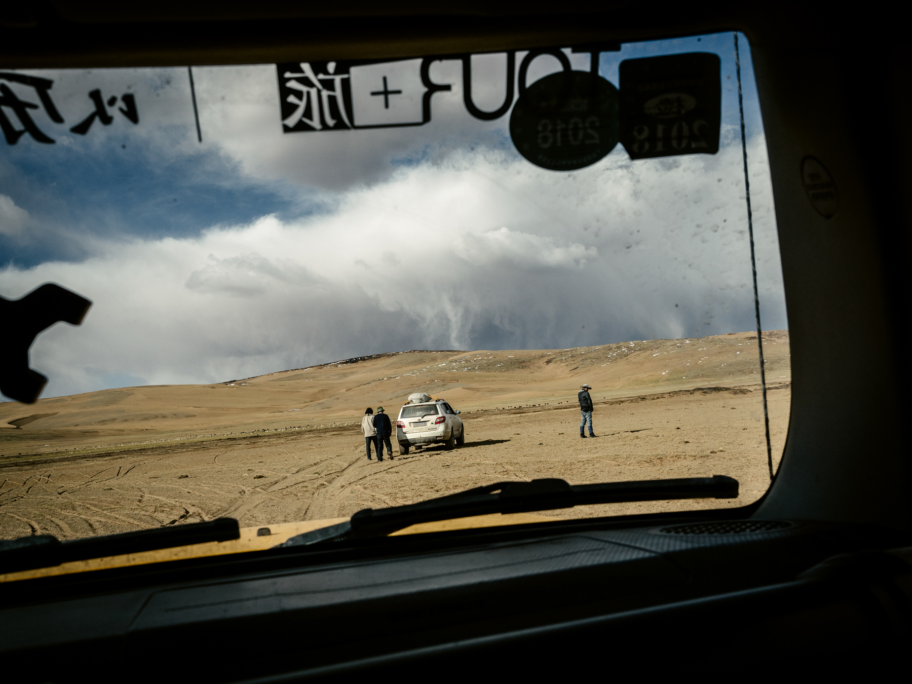 Rain clouds approach in the desert as the team is en route to a campsite near a tributary of the Yellow River. Animals graze at the edge of a grassland.