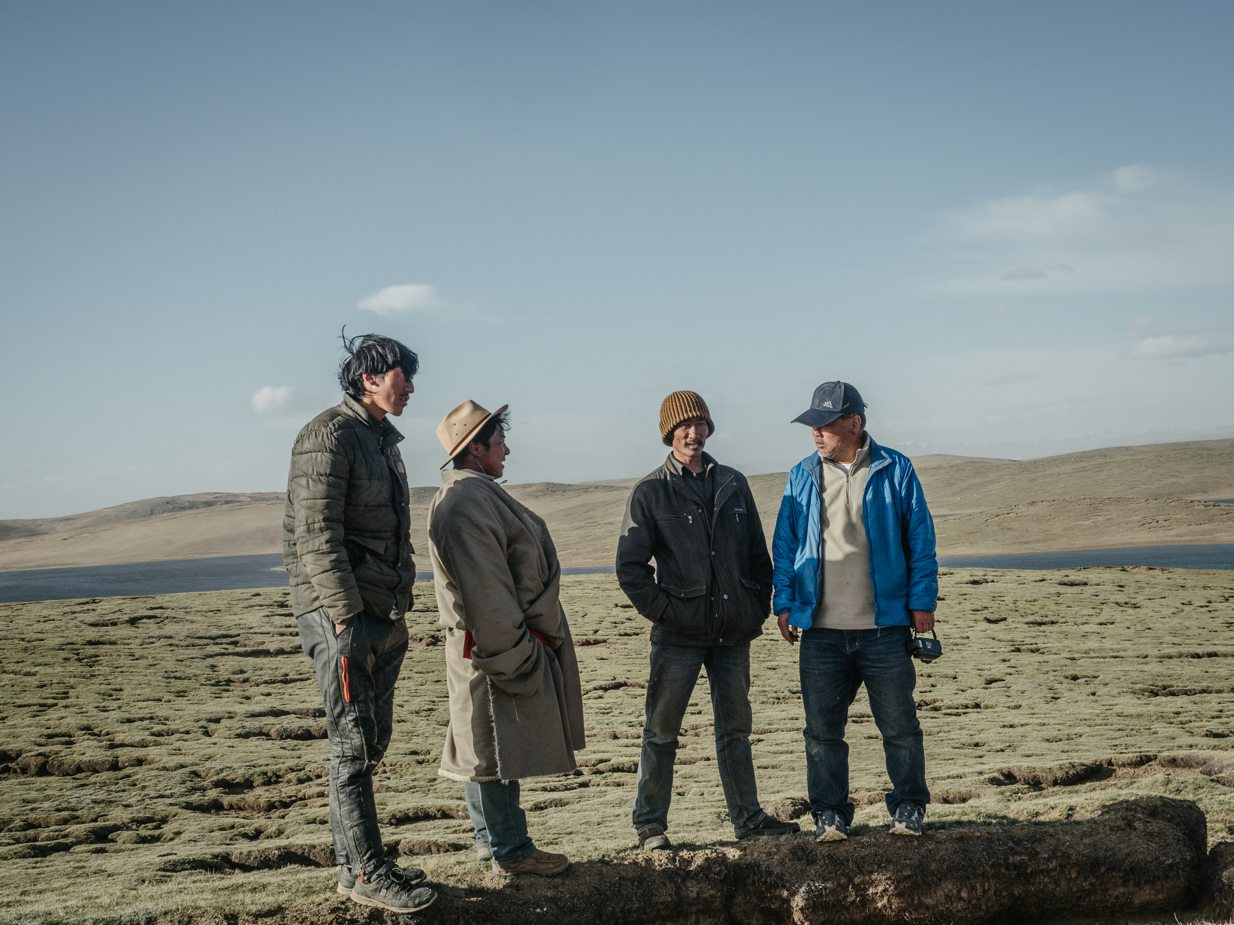 Local Tibetans (left three) greet Yang at the campsite next to the lakes Gangnagemacuo and Rigecuochama. The ground that they stand on shows visible cracks, with sections of the frozen ground having melted and collapsed. This exposes the thin layer of fertile soil to strong winds and burrowing animals, like hares and pikas, causing further degradation and eventual desertification. Yang says that climate change is accelerating desertification of the mountain grasslands.