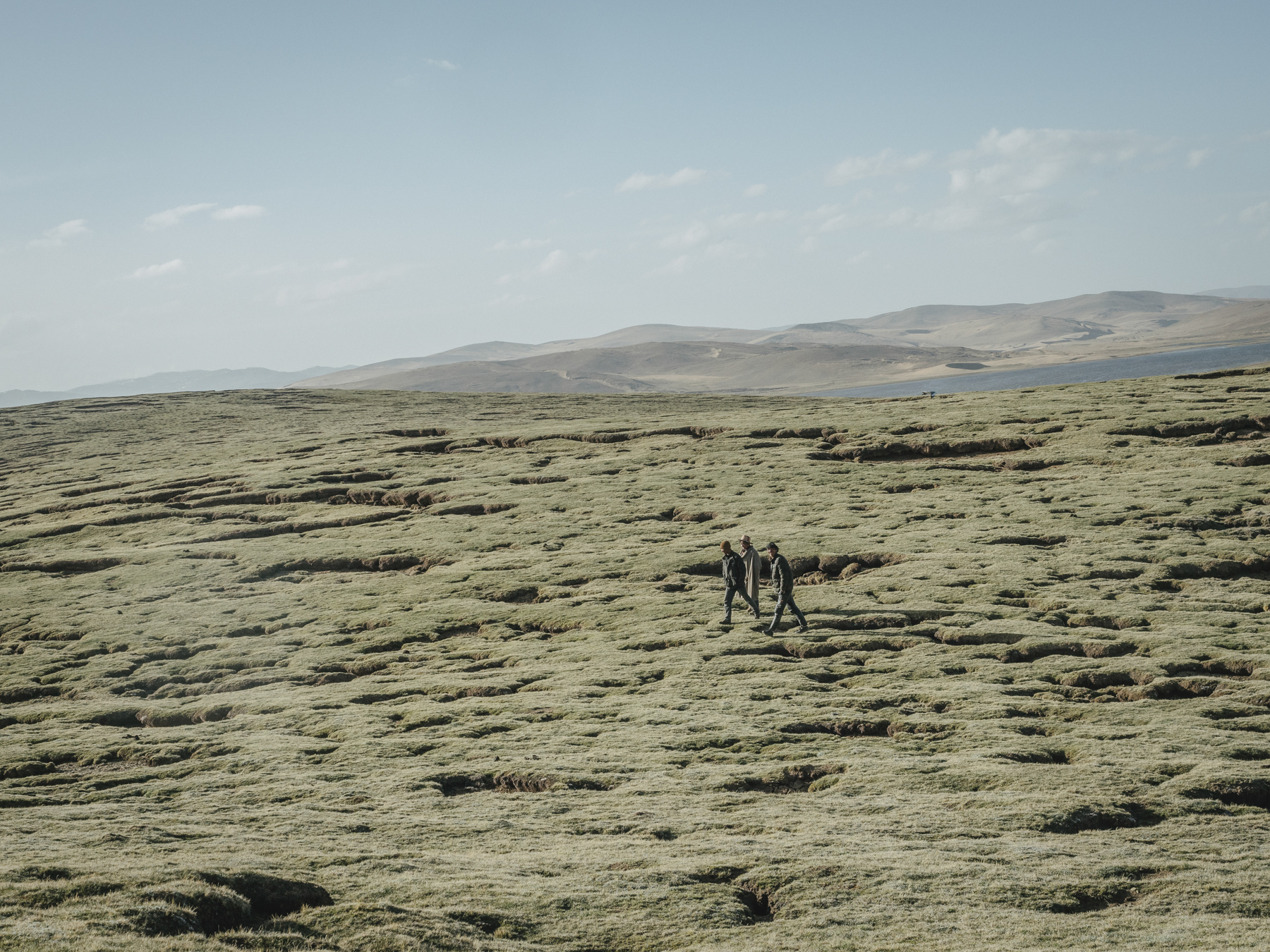 "Local Tibetans walk across the grasslands between Gangnagemacuo and Rigecuochama. ""The grassland here may look green and healthy, but the pockmarked cracks in the grass are the first signs of desertification starting,"" says Yang."