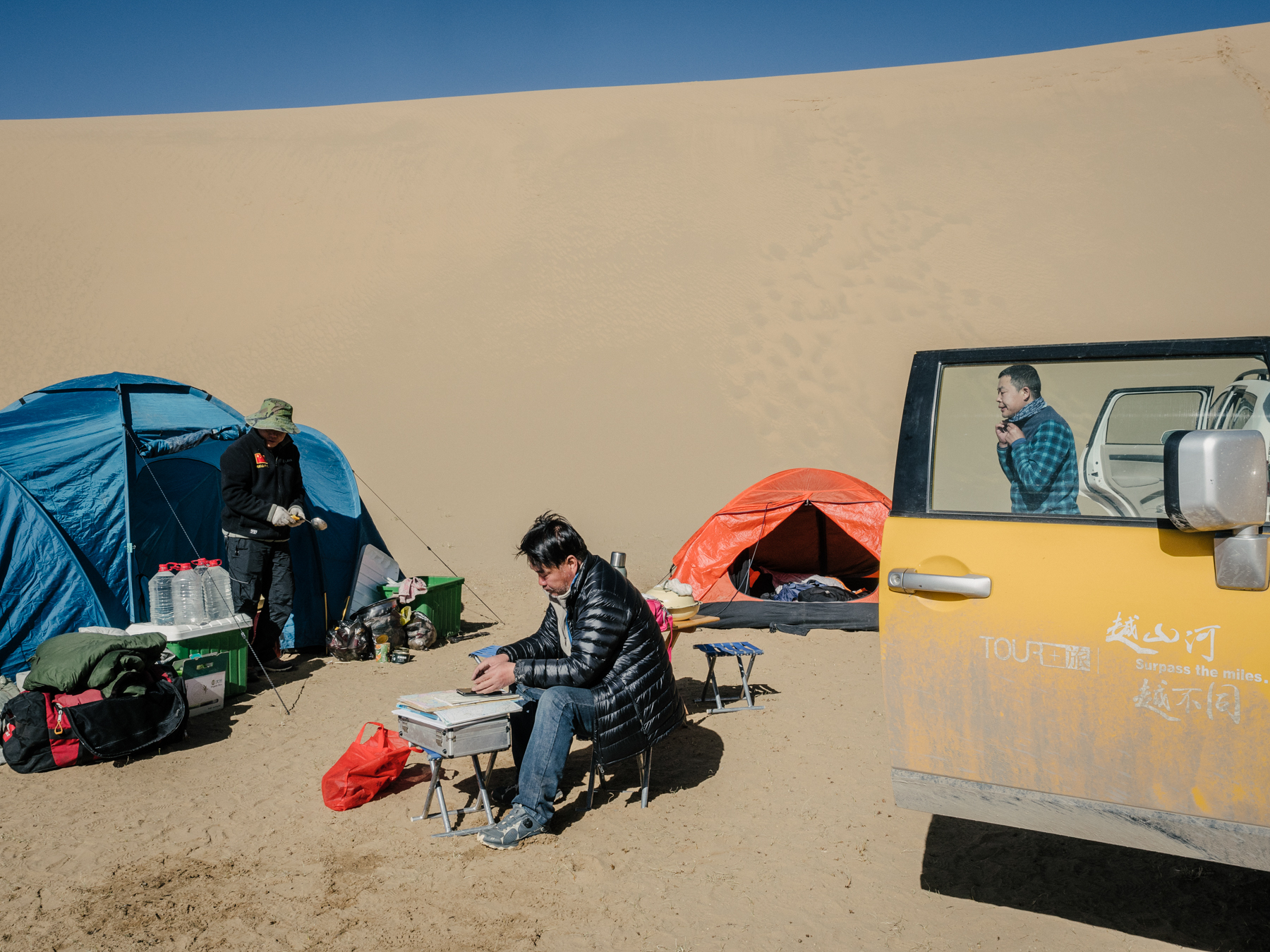 Yang looks at his phone, which displays maps and satellite images of the region near Rigecuochama, a lake off of the Yellow River, in Madoi county. Headwaters of the Yellow River originate in Madoi. The county is severely affected by desertification, with 35% of its land now desert.