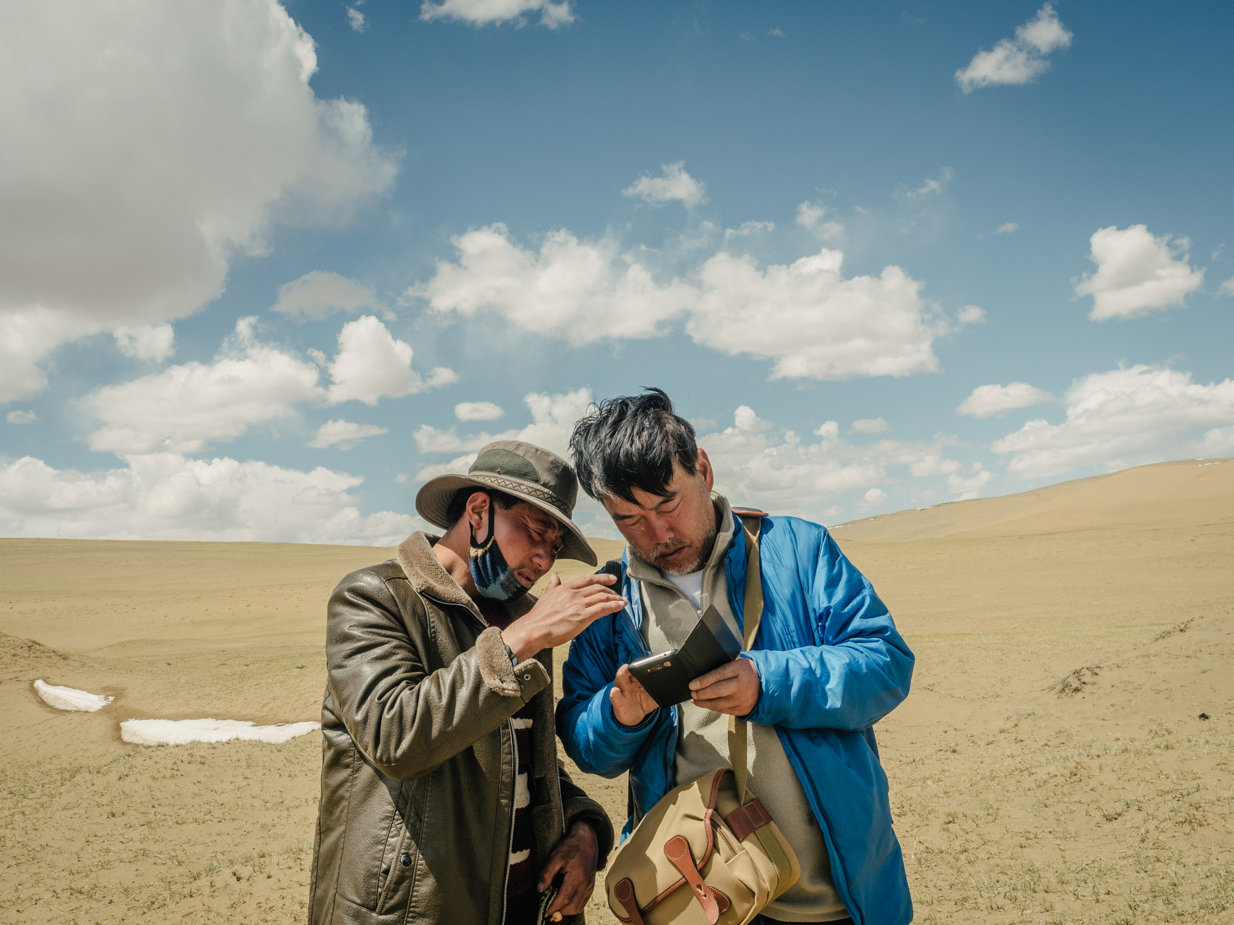 "Yang and a Tibetan herdsman discuss their location on a satellite map, in Madoi county. ""Although satellite imaging has documented the advance of these deserts above an altitude of 4,000 meters [13,000 feet],"" Yang says, ""there are rarely any expeditions to or studies of these newly formed deserts."" As far as he is aware, Yang is the only person who regularly conducts field studies in these areas to assess advancing desertification."