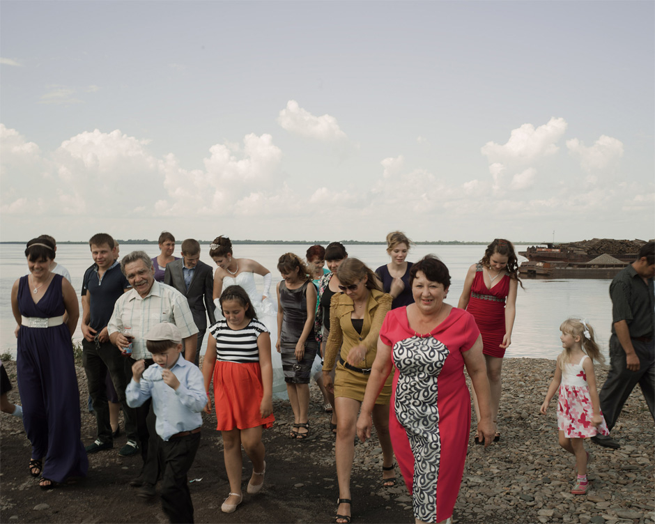 A Russian bride and groom celebrate with members of their wedding party on the banks of the Amur River in Troitskoye, Khabarovsk Krai.
