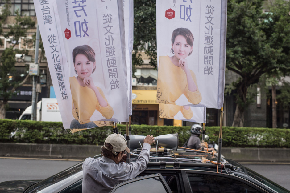 A campaign worker rigs a loudspeaker atop the car of Legislative Yuan candidate Zhou Fang-ru in Taipei.