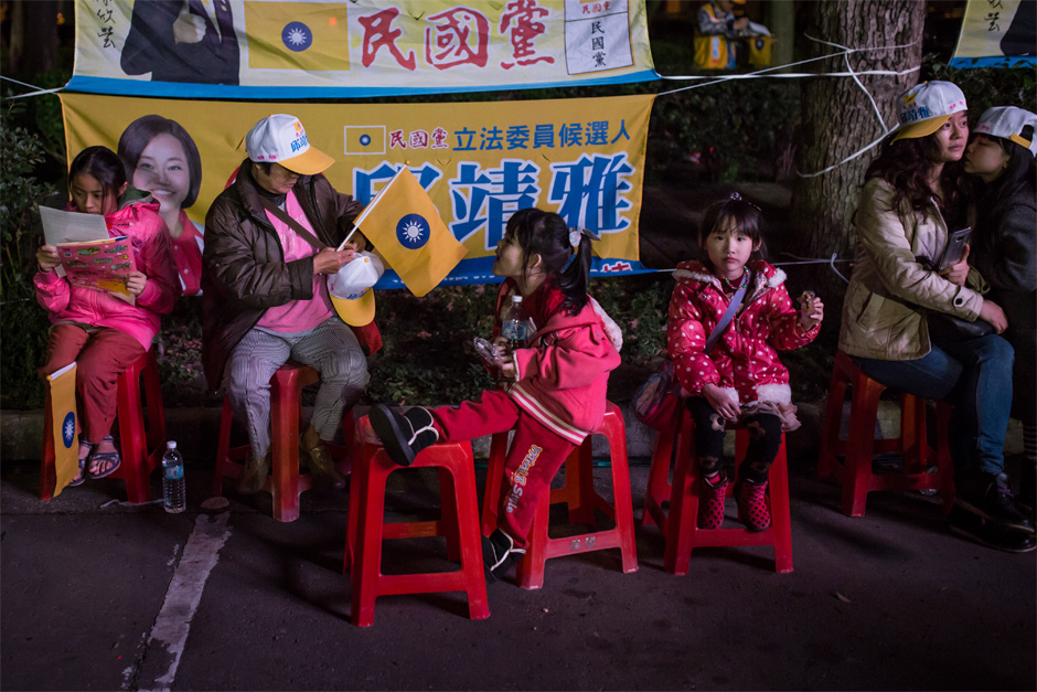Minkuotang supporters young and old wait on the edge of a rally in Zhubei City.