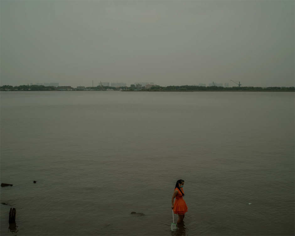 A woman wears a facemask and holds a fishing net while standing knee-deep in the Songhua River in Harbin. A tributary of the Amur, the Songhua is another point of connection between the two countries. An explosion at a Chinese chemical plant in November 2005 spilled 100 tonnes of nitrobenzene into the Songhua—a spill local officials were unable to conceal when it became clear the pollutants would quickly drain across the border into Russia.