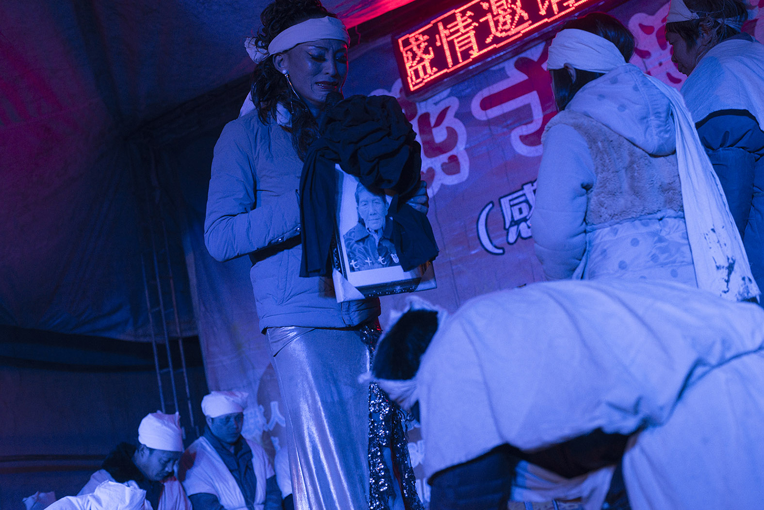Liangzi holds a portrait of a deceased woman and wails, January 28, 2015.