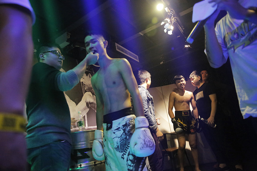 The MC (right) introduces Bo (second-left) and Xia (back, middle), as they prepare for the fight.