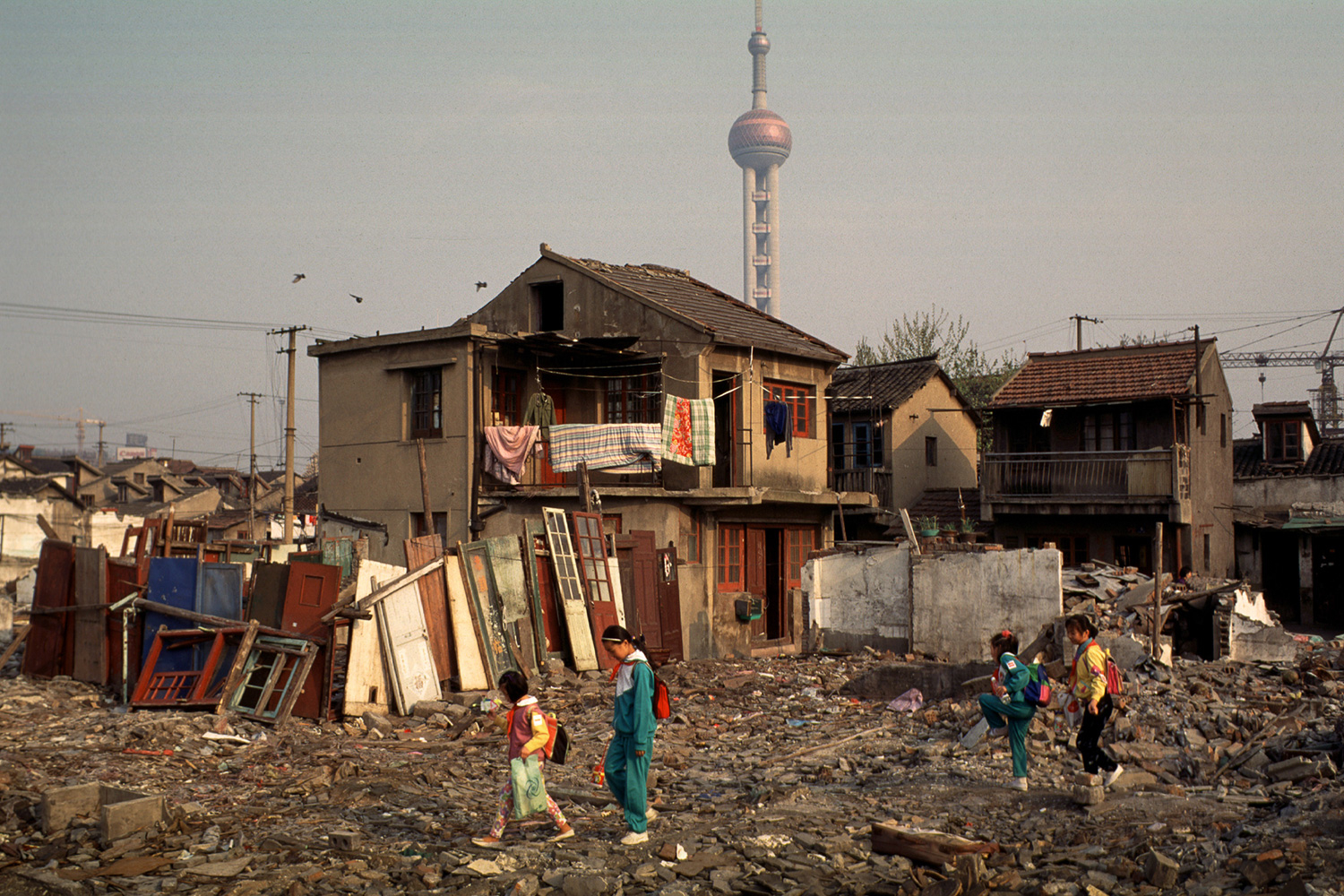 On their way to school, children pass through the rubble of demolished homes in their neighborhood in Lujiazui, 1996.