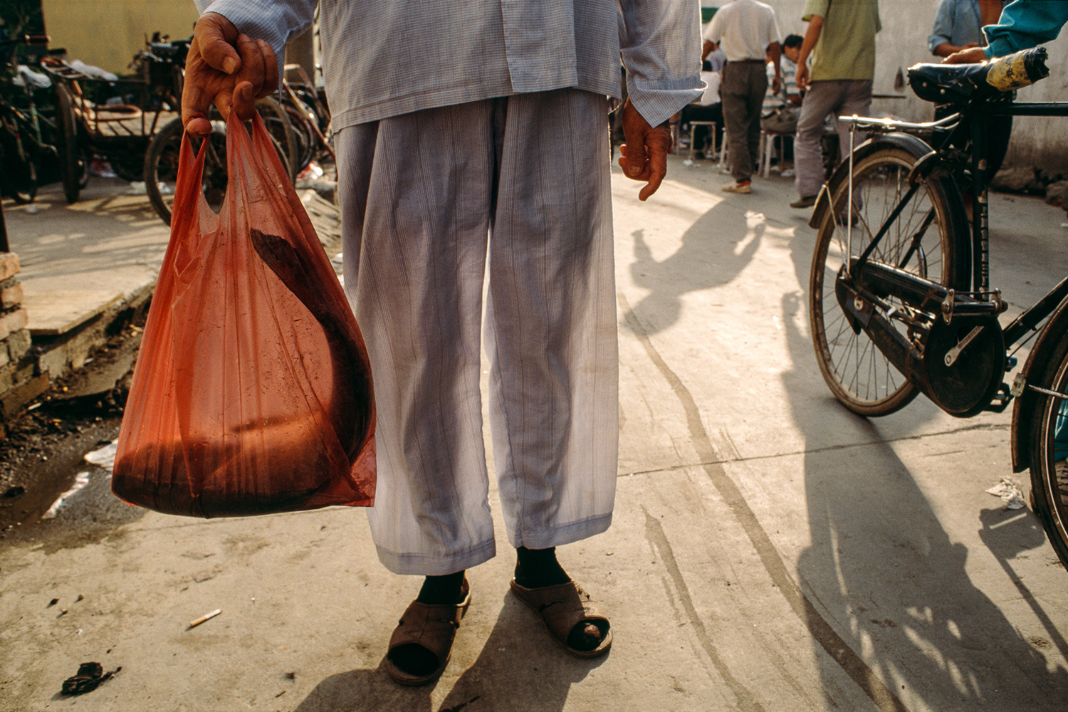Dressed in his pajamas, a man leaves an open air market in Lujiazui with a fresh fish, 1997.