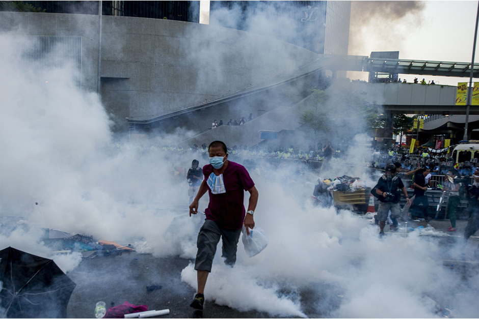 A pro-democracy demonstrator runs as police fire tear gas on September 28 near government headquarters in the Admiralty District. (Photo by Xaume Olleros/AFP/Getty Images)