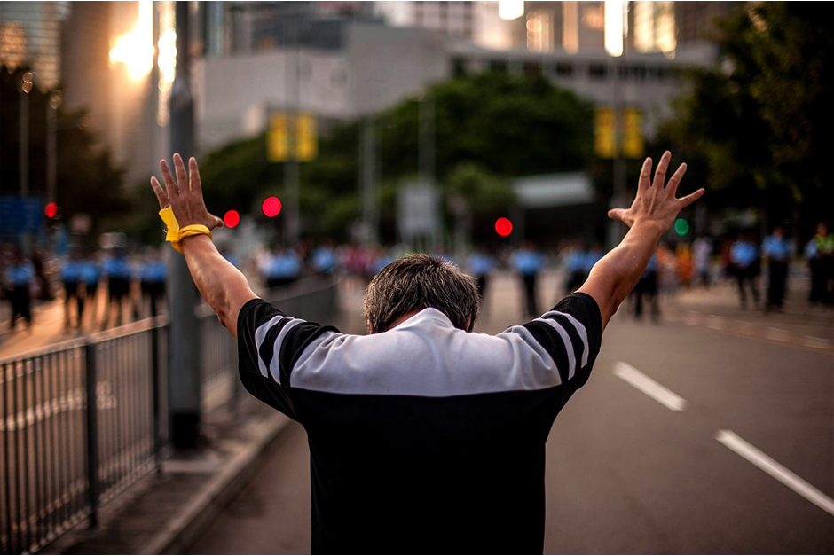 A man raises his hands toward a police line outside of the government complex. (Photo by Anthony Kwan/Getty Images)