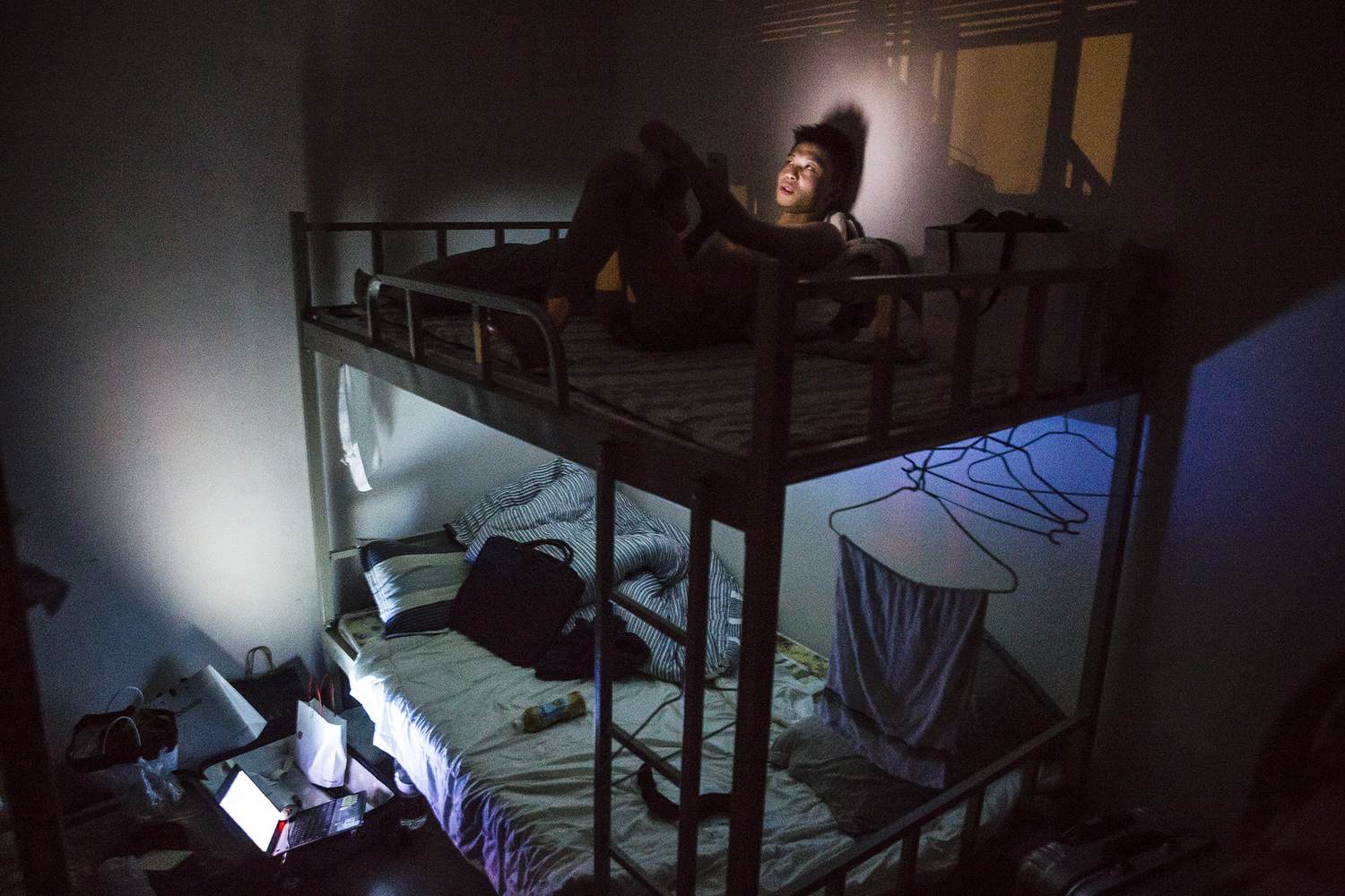 An employee at a technology company in Chongqing rests in the dormitory after the day's courses, May 18, 2015. He said he couldn't find a girlfriend because he was too shy towards women. He participated in Puamap because his family wanted him to get married.