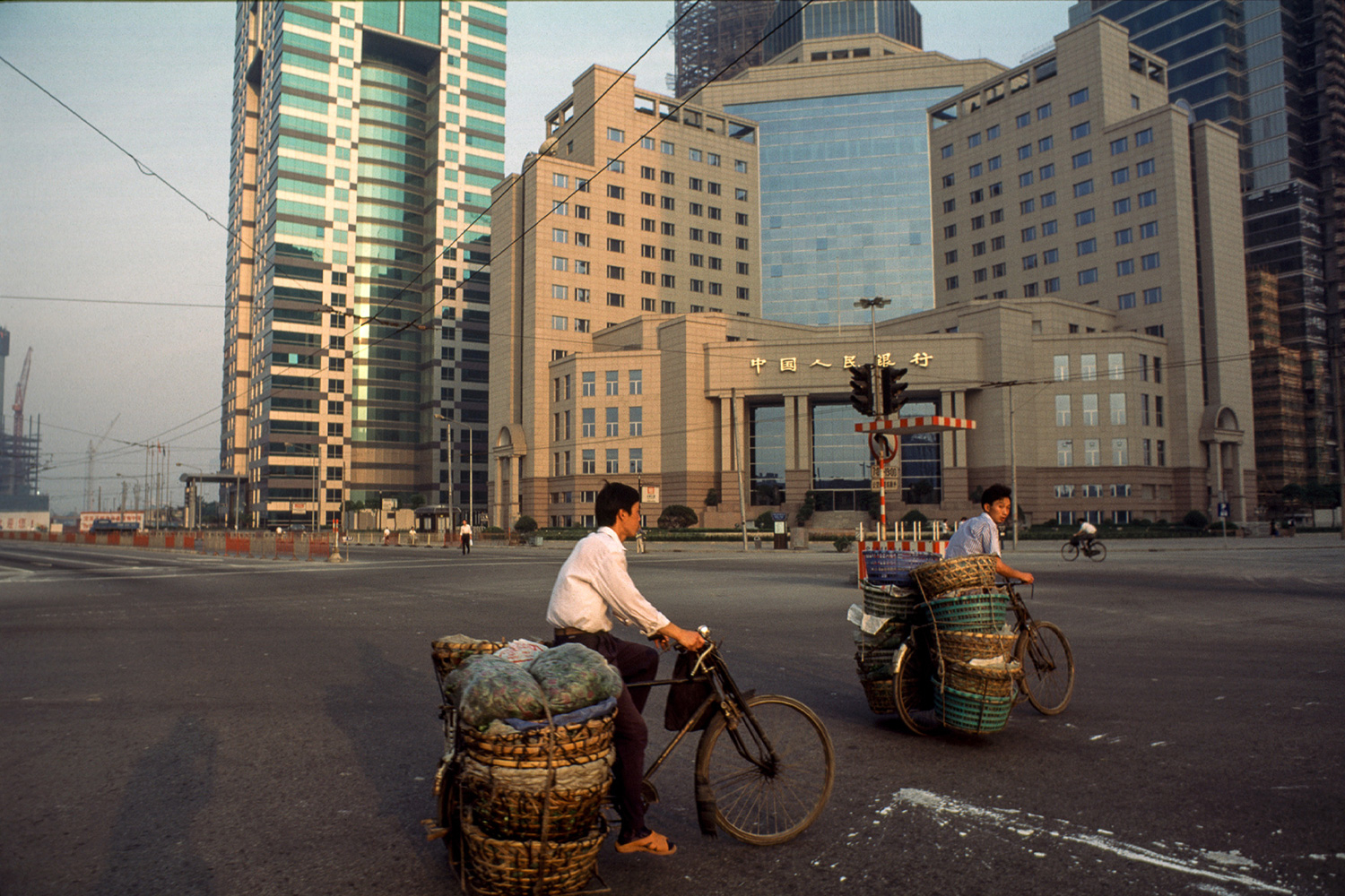 Farmers pedal their produce by bicycle past the yet unopened People's Bank of China, 1996.