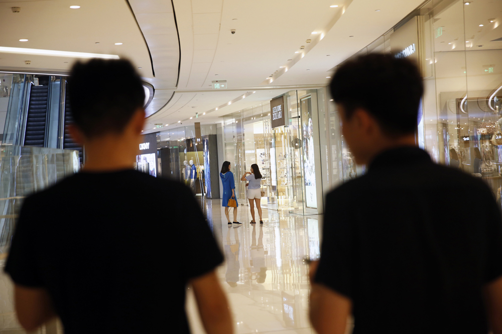 Mentor Lao Tong (left) and a student search for 'targets' to approach at a shopping mall, May 17, 2015.