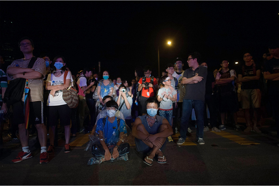 Protesters sit on a street during a pro-democracy protest. (Photo by Anthony Kwan/Getty Images)