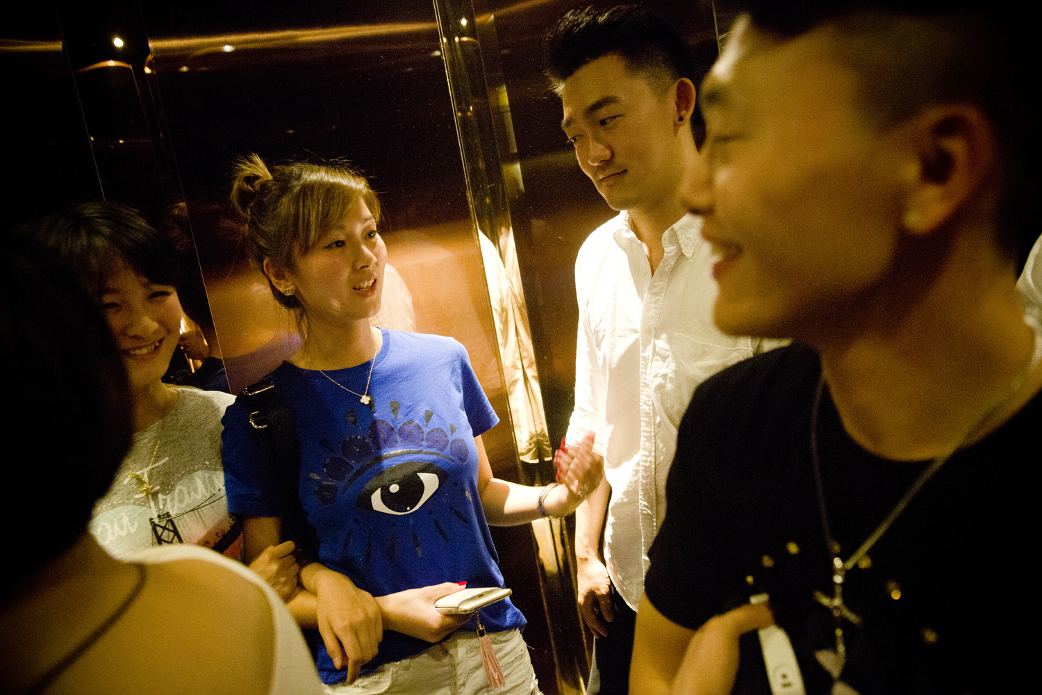 Two mentors chat with women they invited in the elevator as they leave the karaoke bar, just past midnight of May 18, 2015.