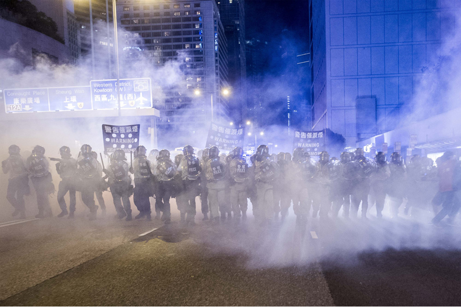 Police officers stand in a cloud of tear gas. (Photo by Xaume Olleros /AFP/Getty Images)