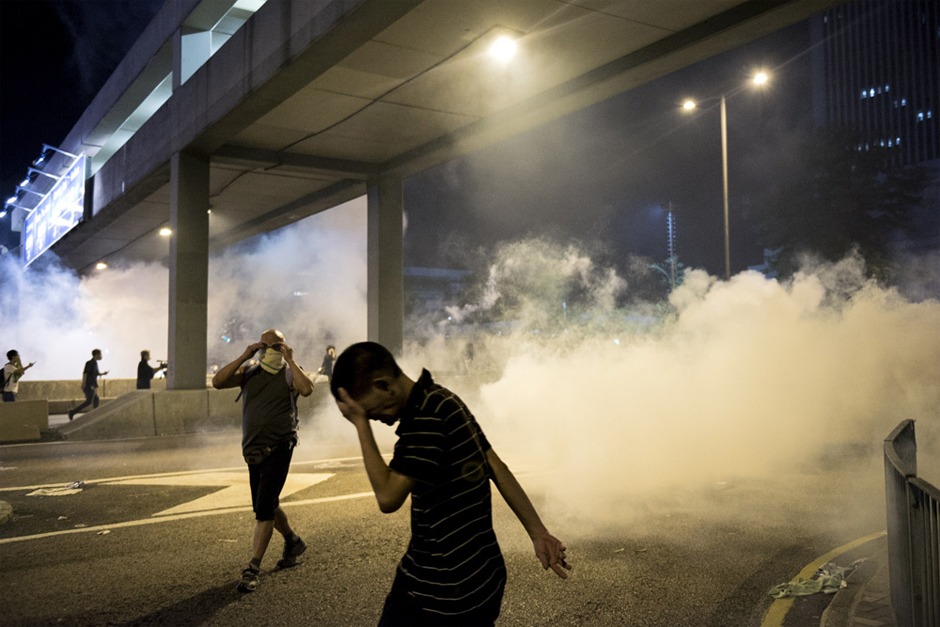 Pro-democracy protesters run away from tear gas fired by the police. (Photo by Alex Ogle/AFP/Getty Images)