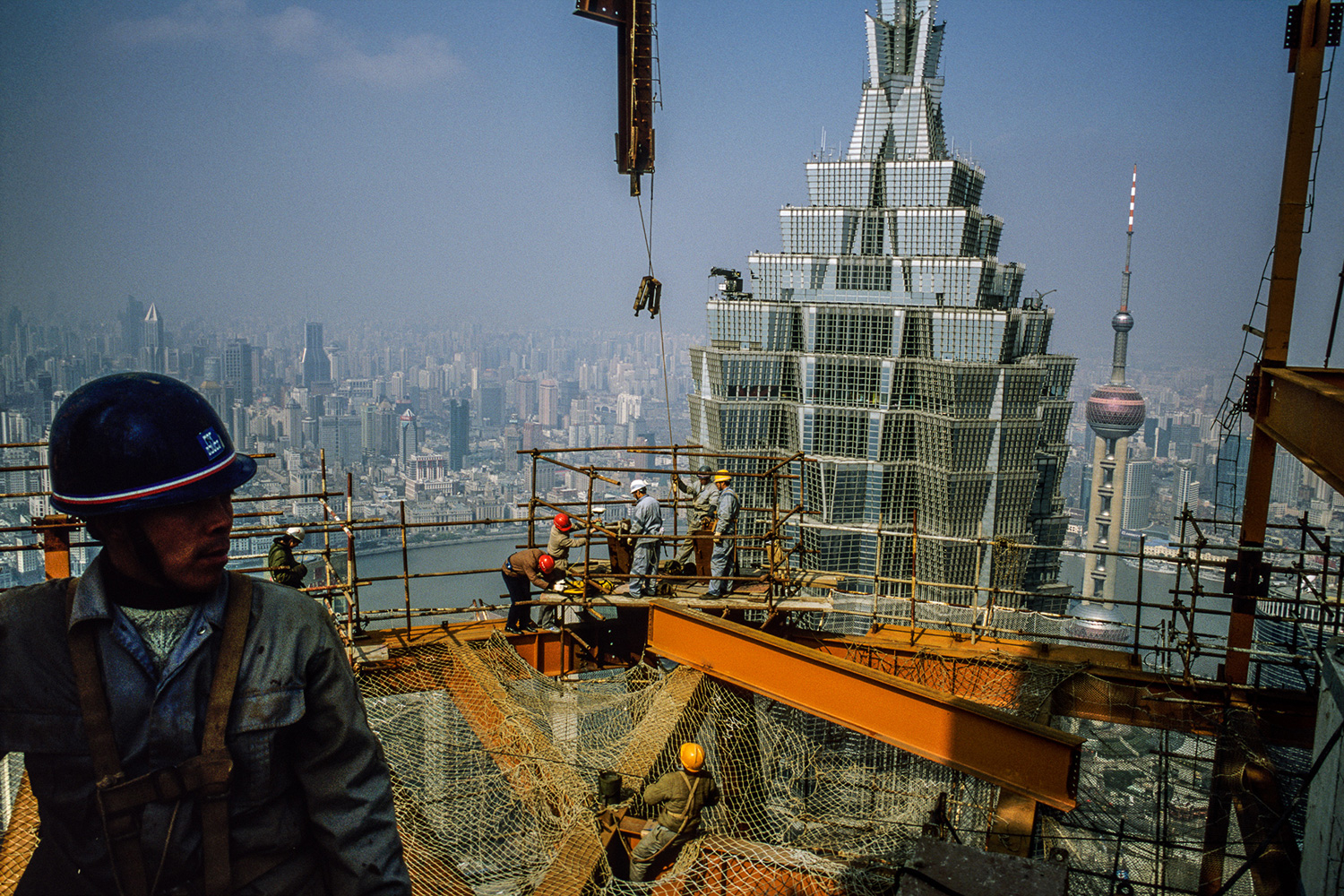 Steel workers from Sichuan set beams on the 88th floor of the Shanghai World Financial Center superstructure under construction in Lujiazui, 2007.