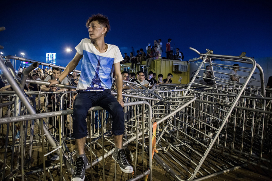 A protester sits on top of barricades used to block the road. (Photo by Lam Yik Fei/Getty Images)