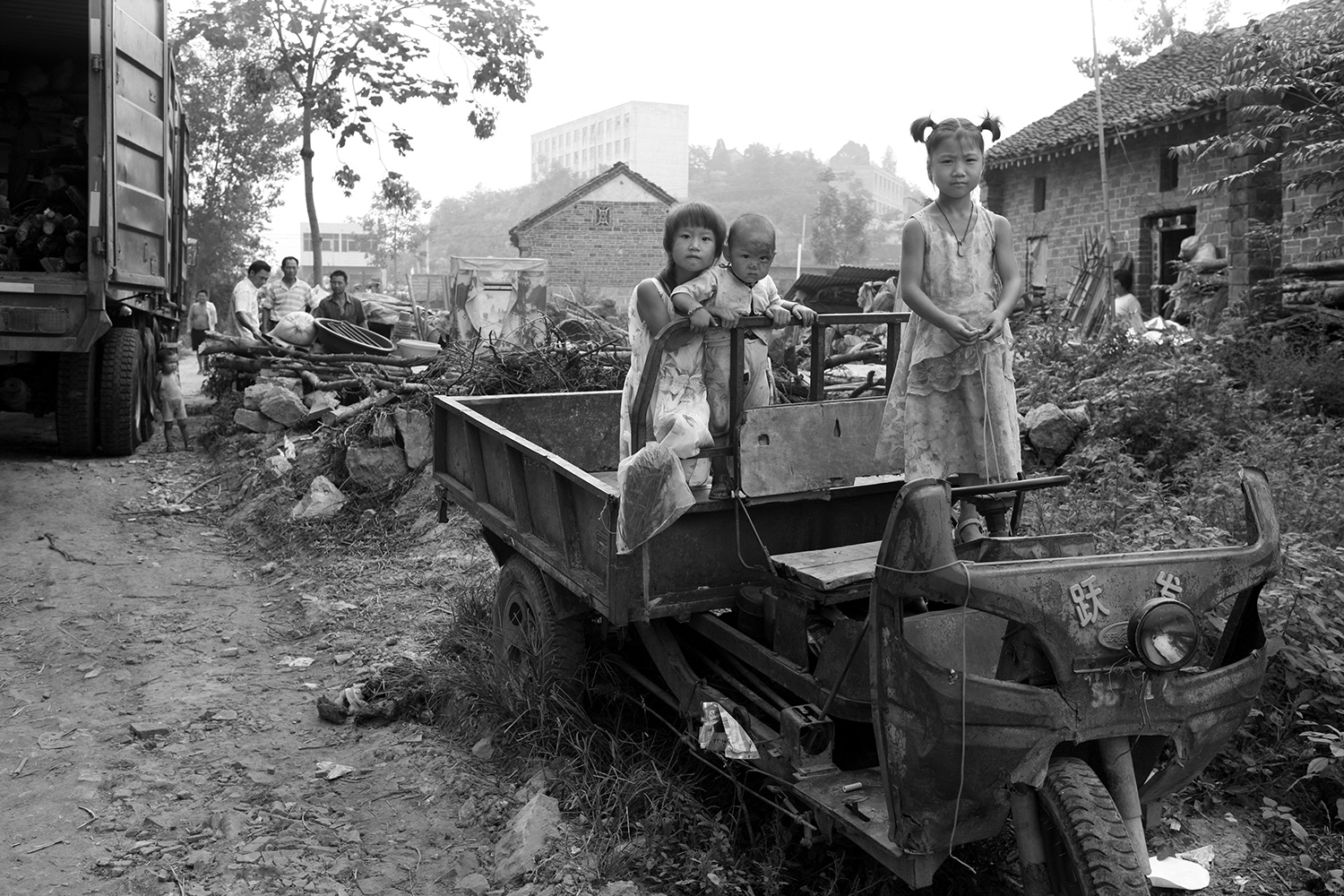 Three children stand in their family's utility vehicle at a demolition site in Jinhe, Xichuan county, Henan province, August 2011, as villagers prepared to move out as part of a relocation program.