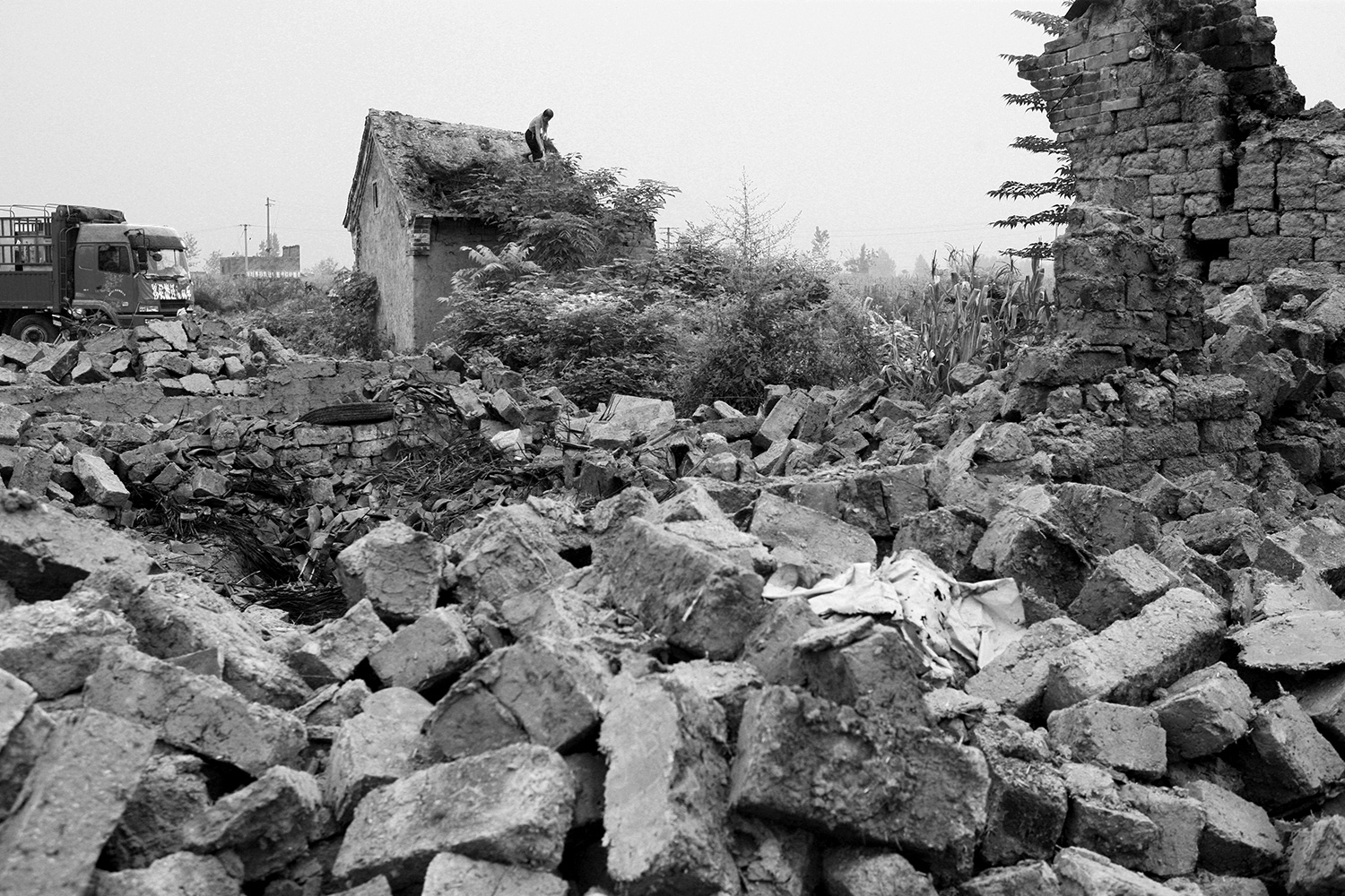 A farmer demolishes his own house in Jinhe. Roof tiles that could be salvaged were loaded onto a truck and taken away.
