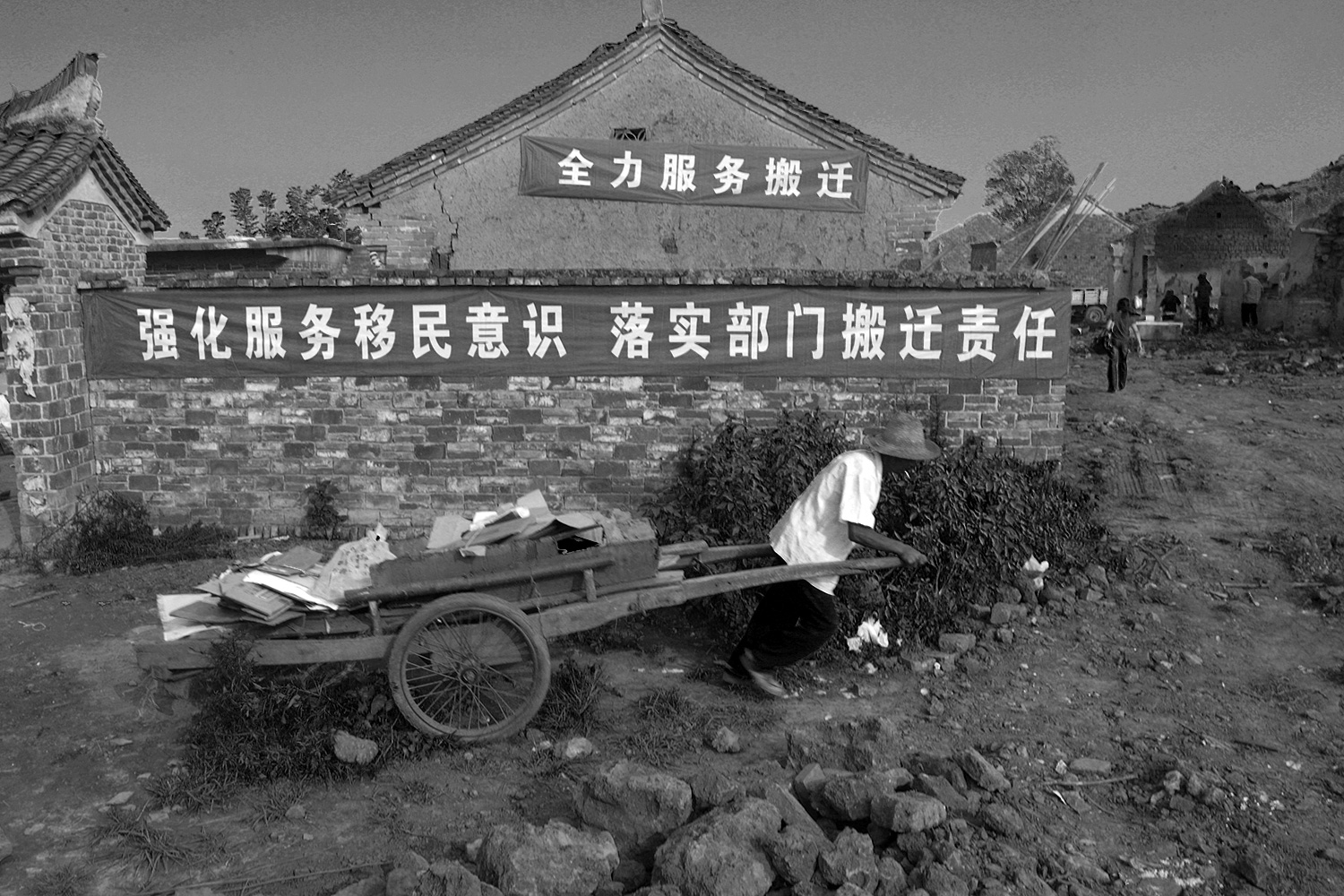 "Under banners that read ""Wholeheartedly Support Relocation"" and ""Strengthen Your Awareness to Serve Migrants to Fulfill Relevant Departments' Responsibilities in Relocation,"" a farmer pulls his belongings in a handcart to load them on a truck to transport them to his new home."