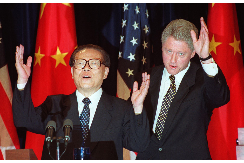 Chinese President Jiang Zemin and U.S. President Bill Clinton wave at the end of their joint press conference, October 29, 1997, at the Old Executive Office Building next to the White House. Jiang came to power in the aftermath of the Tiananmen massacre, an event which caused tense relations between the two countries in the ensuing years. (Photo by Joyce Naltchayan/AFP/Getty Images)
